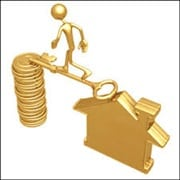 Man on golde key bridging house and stack of gold coins