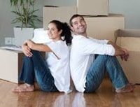 finnance brokers - Couple sitting on floor amongst moving boxes