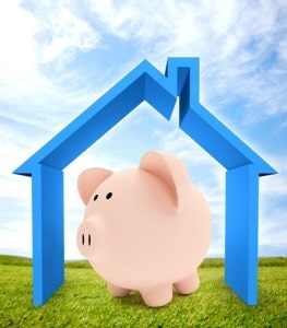 Pink piggy bank set inside the framework of a house