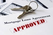 House keys on top of approved loan agreement