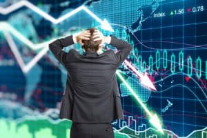man clutches his head in panic as stock market crashes