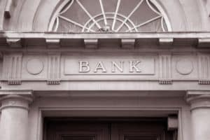 bank sign over entrance door of old style bank building in black and white sepia tone