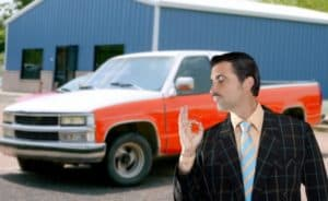 used car salesperson with pencil moustache selling old car as brand new signifying with OK hand gesture that it's perfect