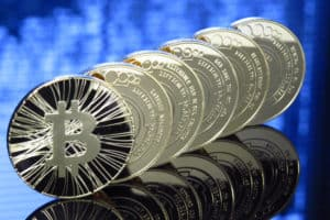 Close-up of 6 bitcoins standing on edge on top of a glass table