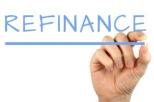 refinance written in light blue capital letters on reverse glass by a mans hand