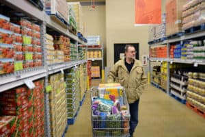 man pushing a supremarket trolling through the aisles of a wholesale grocery market