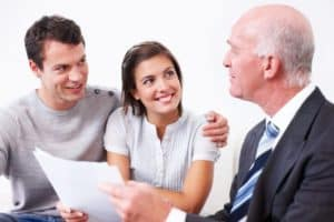professional mortgage broker discussing a mortgage with a young couple