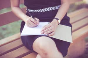 Young business woman planing, writing and reviewing her finances at city park.