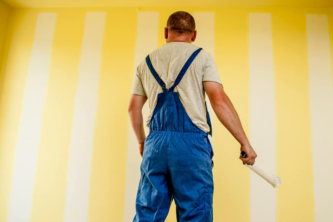 http://mastermortgagebrokersydney.com.au - man in overalls with piant roller painting a room