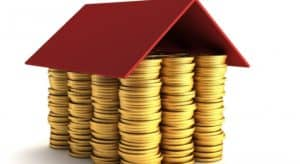 first time home owners loan - piles of coins stacked together with a red roof on top