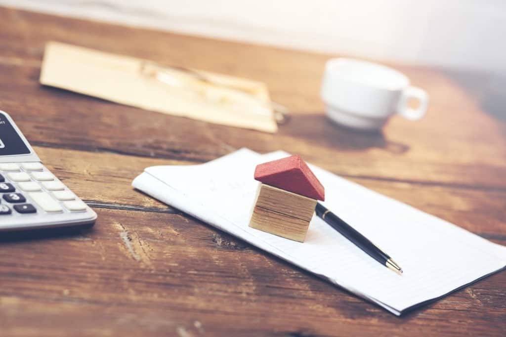 mortgage refinance - calcuilator, notebook, small toy wood house on wooden table. Concept home loan refinance plan
