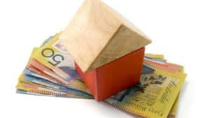 first home owners grant - small toy wooden block house sitting on australian bank notes