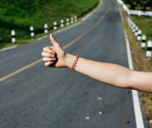 finance broker - photo of a young lady's out stretch arm with thumb up trying to hitch a ride