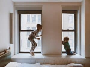 A young boy about 8-9 playing peek-a-boo around a window alcove with his baby brother