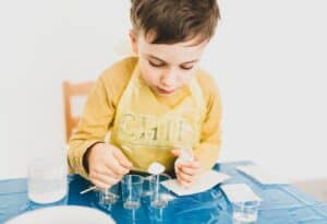 Little boy measuring baking ingredients into small plastic containers
