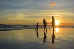 Young family at the beach silhouetted by the setting sun