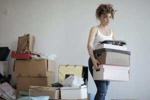 Young woman in jeans carrying boxes to move house