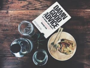 A book titled damn good advice laying on a breakfast table among food, water bottle and glasses