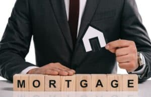 Man in business suit and tie sitting behind scrabble tokens spelling out the word mortgage