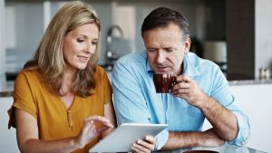 Should I use a mortgage broker middle age customer clients discussing their mortgage options at the kitchen table