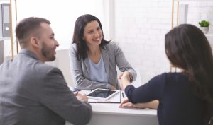 Young woman should I use a mortgage broker congratulating a young couple on their mortgage approval