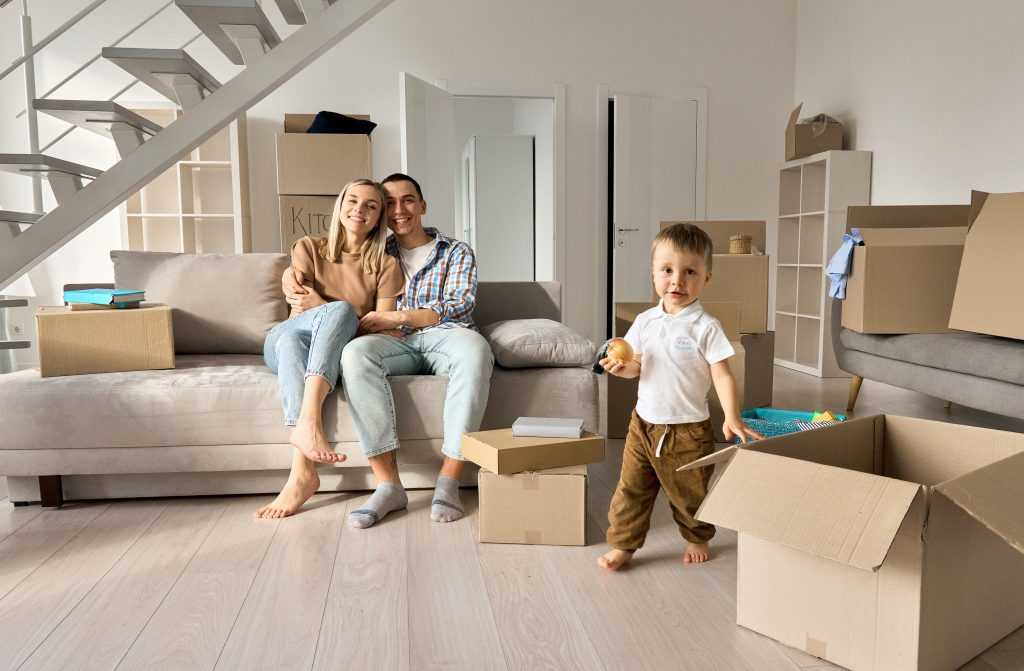 Should I use a mortgage broker happy young couple new home owners with child son in living room on moving in day